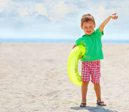 Happy kid with rubber ring on the beach Stock Images