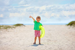 Happy kid with rubber ring on the beach Stock Photos