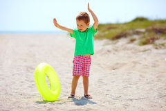 Happy kid with rubber ring on the beach Stock Photo