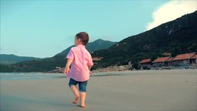 Happy kid running along the beach.Silhouette of children`s Feet walking on wet sand in along a tropical beach on a stock video