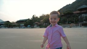Happy kid running along the beach.Silhouette of children`s feet walking on wet sand in along a tropical beach on a stock video footage