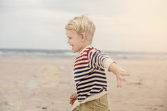 Happy kid running on the sea beach. Oudoor portrait Stock Photo