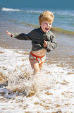 Happy kid running on the sea beach Royalty Free Stock Images