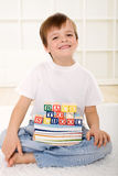 Happy kid with school books sitting on the floor Royalty Free Stock Photography