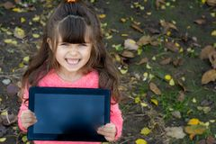 Happy kid showing tablet as if advertising it, and standing over autumn background royalty free stock photography