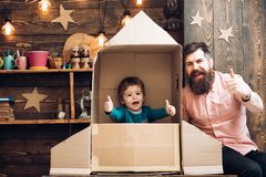 Happy kid sit in cardboard hand made rocket. Parenthood concept. Boy play with dad or father, little cosmonaut sit in. Rocket made out of cardboard box. Child royalty free stock photo