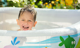 Happy kid sits wet in the inflatable pool in the garden in summer, Stock Photos