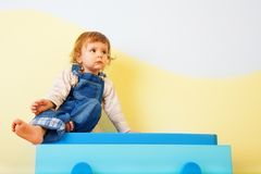 Happy kid sitting on the furniture Stock Images