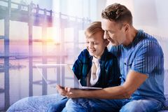 Happy kid sitting near his father. Family day. Attentive men embracing his son and bowing head while holding laptop on left arm Royalty Free Stock Photo