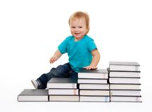 Happy kid sitting on the steps of books Royalty Free Stock Images