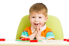 Happy kid sitting at table playing with clay Royalty Free Stock Images
