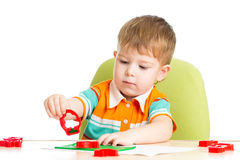 Happy kid sitting at table playing with clay Royalty Free Stock Photo