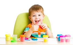 Happy kid sitting at table playing with clay Royalty Free Stock Image
