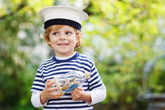 Happy kid in skipper uniform playing with toy ship. Against green tree summer background royalty free stock images