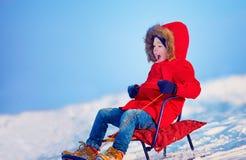 Happy kid sliding downhill on winter snow Stock Photography