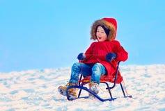 Happy kid sliding downhill on winter snow Royalty Free Stock Photography