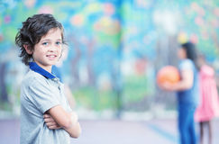 Happy kid smiling in schoolyard with other chilldren playing on. Background Stock Images