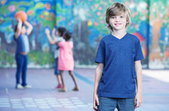 Happy kid smiling in schoolyard with other chilldren playing on. Background Royalty Free Stock Photos