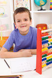 Happy kid solving math exercise. Happy boy solving math exercises in his room royalty free stock photos