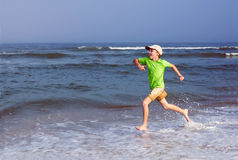 Happy kid sticking his tongue runs along the sea on the surf Royalty Free Stock Photo