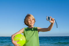Happy kid on summer holiday taking selfie photo stock photo