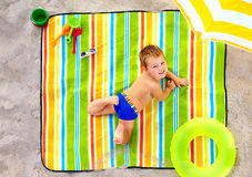 Happy kid sunbathing on colorful beach Stock Photos