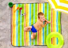 Happy kid sunbathing on colorful beach Stock Photos