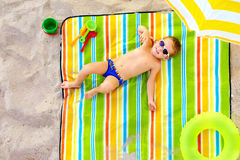 Happy kid sunbathing on colorful beach Stock Images