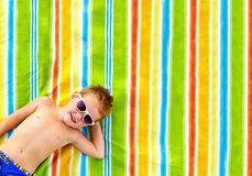 Happy kid sunbathing on colorful blanket Royalty Free Stock Photography