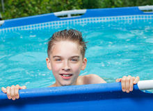 Happy kid in a swimming pool outdoors Stock Image
