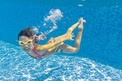 Happy kid swimming underwater in pool Royalty Free Stock Photo