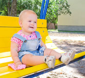 Happy kid on a swing. Happy cute kid sitting on a yellow swing at the playground royalty free stock image