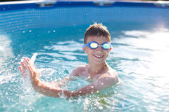 Happy kid with teeth smile splasing in swimming pool. Enjoying summer holiday Royalty Free Stock Images