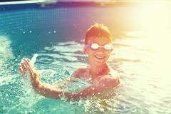 Happy kid with teeth smile splasing in swimming pool vintage sty. Happy kid with teeth smile splasing in swimming pool, enjoying summer holiday, vintage style Royalty Free Stock Photos