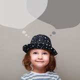 Happy kid thinking and looking up on chat bubbles above. On grey background Stock Images