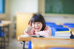 Happy kid thumb up with book. In class Stock Photos