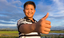 Happy kid with thumbs-up gesture Stock Image