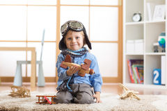 Happy kid toddler playing with toy airplane and dreaming of becoming a pilot Royalty Free Stock Photos
