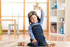 Happy kid toddler playing with toy airplane and dreaming of becoming a pilot Royalty Free Stock Photo