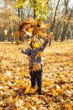 Happy kid tossing many leaves Stock Photos