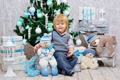Happy kid with toys by the Christmas tree Royalty Free Stock Image