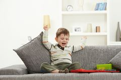 Happy kid with toys sitting on sofa hands in air. Happy little caucasian kid with toys sitting on sofa, looking at camera, smiling. Home indoors, hands in air Royalty Free Stock Photo