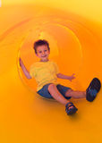 Happy kid in a tube slide Royalty Free Stock Photo
