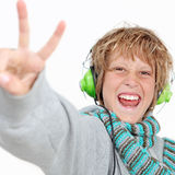 Happy kid v sign. Happy kid doing v sign and listening to music wearing headphones Royalty Free Stock Image