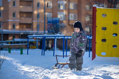 Happy kid walking outdoors in winter city drags his sled. child smiling and having fun. Royalty Free Stock Image