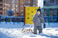 Happy kid walking outdoors in winter city drags his sled. child smiling and having fun. Stock Images
