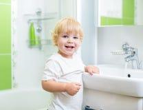 Happy kid washing hands in bathroom Royalty Free Stock Photos