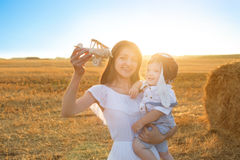 Happy kid and woman playing with toy airplane against field. Royalty Free Stock Photo