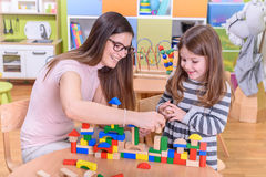 Happy Kid With Young Teacher Playing in Kindergarten. Happy Kid and Kindergarten Teacher Playing with Toy Blocks Stock Images