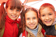 Happy kids. Portrait of happy kids looking at camera while under umbrella outside stock image